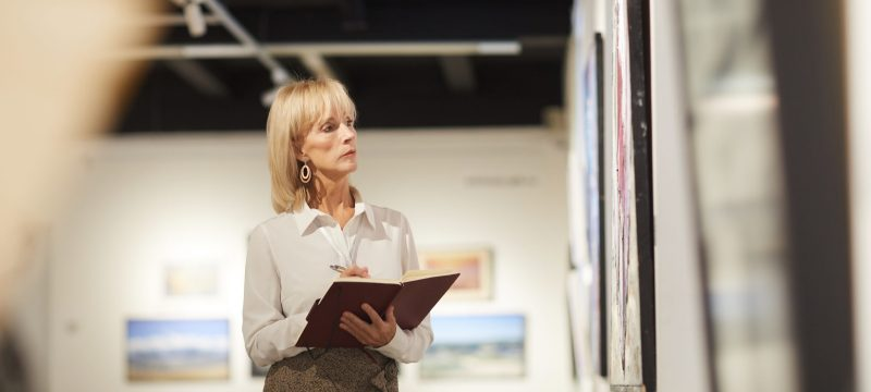 Waist up portrait of elegant mature woman looking at paintings in art gallery hall and enjoying museum exhibition, copy space